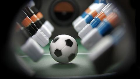 Tischfussballfeld unmittelbar vor dem Anstoß mit Fokus auf den Ball